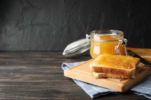Toast met abrikozenjam, bord, handdoek en pot op houten achtergrond, ruimte voor tekst Premium Foto