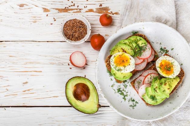 Toast met avocado, radijs, ei en lijnzaad Premium Foto