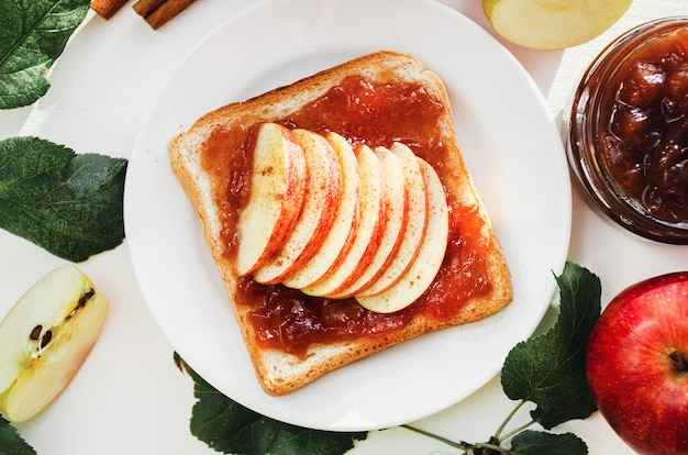 Toast met een geplette appeljam, plakjes verse appels, kaneel op een bord op een witte tafel. Premium Foto