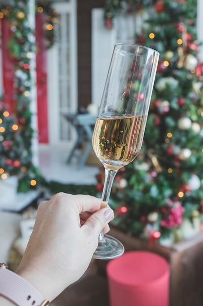 Toast met glas champagne in vrouwelijke hand. new years eve viering. feest, drankjes, vakantie, mensen en feest concept. champagne en nieuwjaar decoratie. party met mousserende wijn Premium Foto