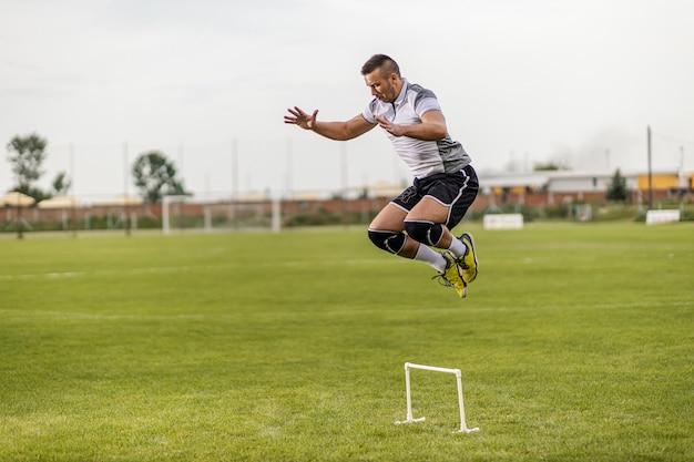 Toegewijde, sterke, aantrekkelijk fitte voetballer die over een obstakel springt. Premium Foto
