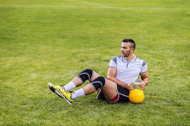Toegewijde, sterke, aantrekkelijke voetballer die in vorm sit-ups doet met een ketelbel terwijl hij op het veld zit. Premium Foto