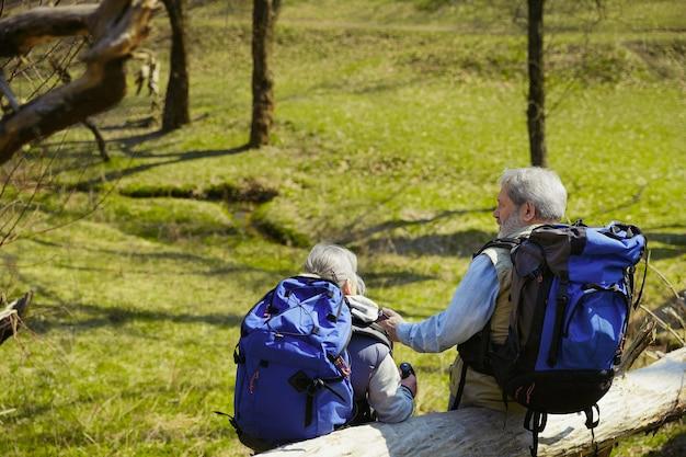 Toekomst plannen. leeftijd familie paar man en vrouw in toeristische outfit wandelen op groen gazon in de buurt van bomen en kreek in zonnige dag. concept van toerisme, gezonde levensstijl, ontspanning en saamhorigheid. Gratis Foto