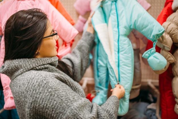 Toekomstige moeder in de winkel voor pasgeborenen, stoffenafdeling. zwangere vrouw in winkel van goederen voor zuigelingen Premium Foto