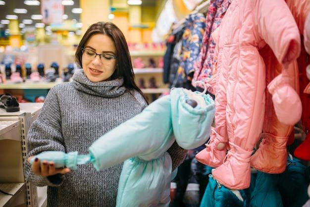 Toekomstige moeder in de winkel voor pasgeborenen Premium Foto