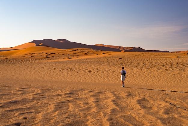 Toerist die op de zandduinen in sossusvlei, namib-woestijn, het nationale park van namib naukluft, namibië lopen. Premium Foto