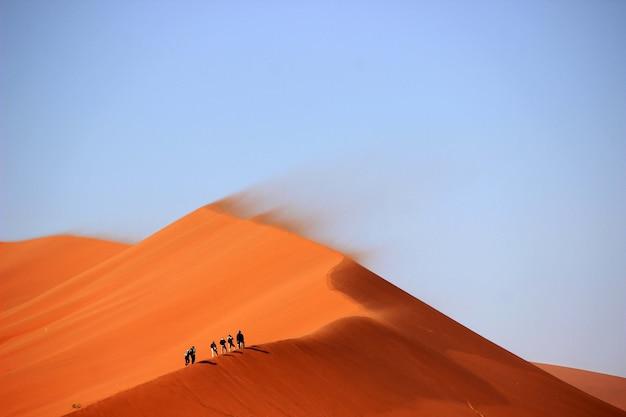 Toeristen beklimmen de zandduinen in de woestijn met de blauwe lucht Gratis Foto