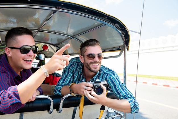 Toeristen die en pret op tuk tuk-taxi in thailand hebben opgewekt zijn Premium Foto