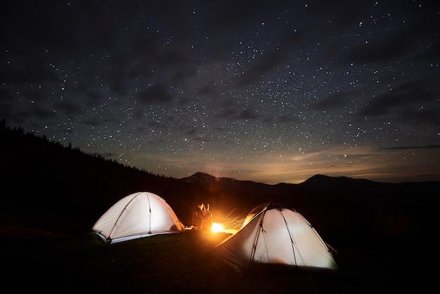 Toeristen in de buurt van kampvuur en tenten onder nachtelijke sterrenhemel Premium Foto