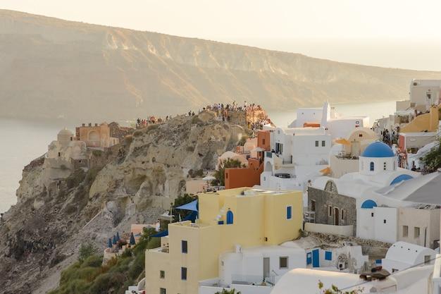 Toeristen ontmoeten de zonsondergang in het dorp oia, santorini. Premium Foto