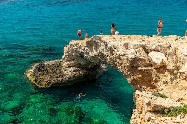 Toeristen springen van een hoogte in de azuurblauwe wateren van de middellandse zee. Premium Foto