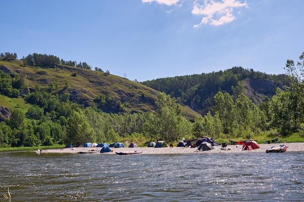 Toeristenkamp aan de rivier. tenten onder de blauwe lucht. raften op een bergrivier. Premium Foto