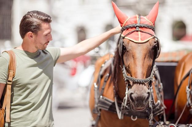 Toeristenmens die van een wandeling door wenen genieten en de twee paarden in het vervoer bekijken Premium Foto