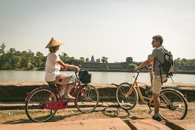 Toeristenpaar het cirkelen in angkor-tempel, kambodja. de hoofdvoorgevel van angkor wat overdacht watervijver. eco-vriendelijk toerisme reizen. afgezwakt Premium Foto