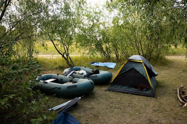Toeristentent, opblaasbare boten in het boskamp tussen de bomen. Premium Foto