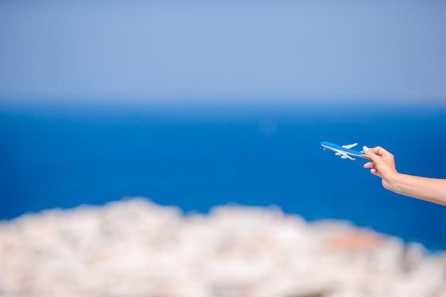 Toeristenvrouw met stuk speelgoed vliegtuig in handenachtergrond het oude griekse dorp Premium Foto