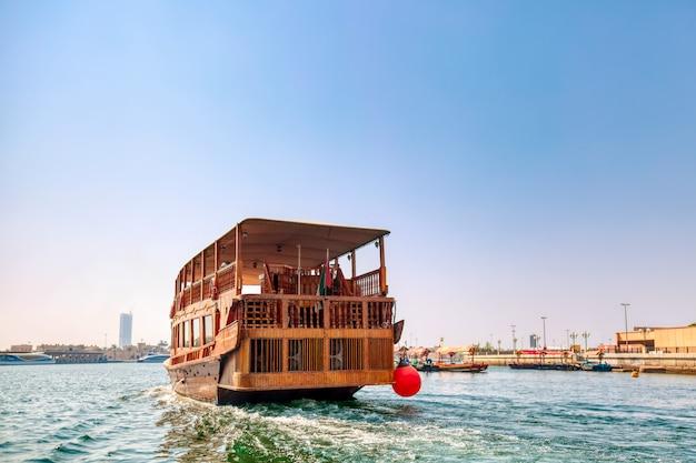 Toeristische houten schip in dubai creek baai op een zonnige zomerdag. verenigde arabische emiraten. Premium Foto