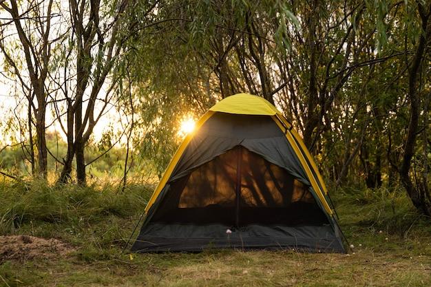 Toeristische tent in een boskamp tussen de bomen bij zonsondergang. Premium Foto