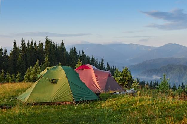 Toeristische tenten staan in het groene mistige bos bij de bergen. Gratis Foto