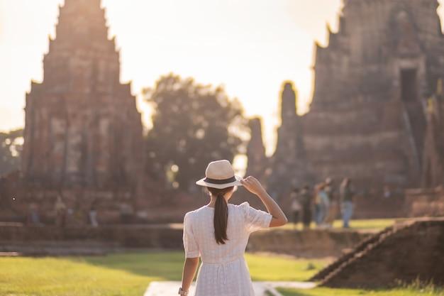 Toeristische vrouw in witte jurk een bezoek aan oude stoepa in wat chaiwatthanaram tempel in ayutthaya historical park, zomer, azië en thailand reizen concept Premium Foto