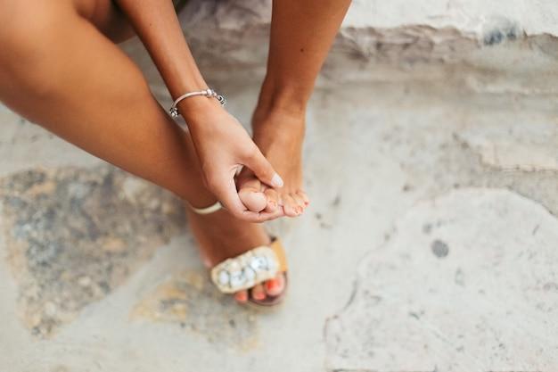 Toeristische vrouw met zere voeten en blaren controleert haar pijnlijke voeten. Premium Foto