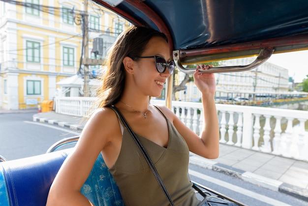 Toeristische vrouw verkennen van de stad bangkok met tuk tuk taxi Premium Foto