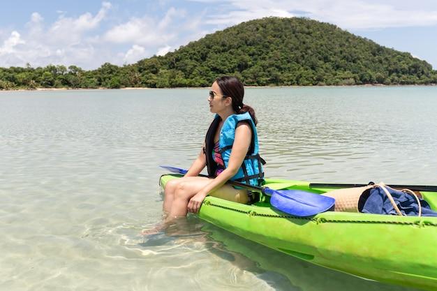 Toeristische vrouw zittend op kajak lookign op prachtig tropisch strand op vakantie. Premium Foto