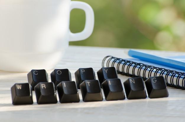 Toetsen op de tafel, het woord copywriting, notebook, potlood, beker Premium Foto