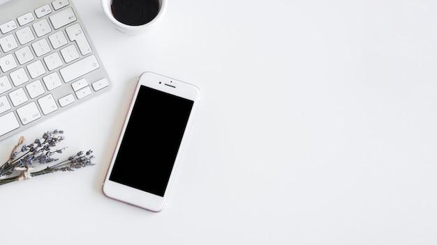 Toetsenbord dichtbij smartphone, installaties en kop van drank Gratis Foto