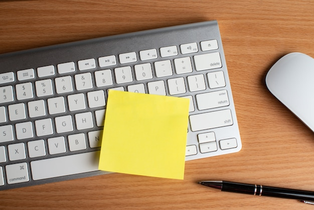 Toetsenbord en muis met gele blocnotes en zwarte pen Premium Foto