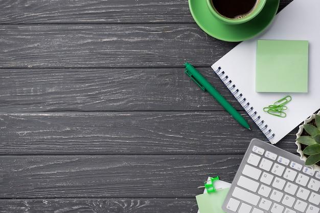 Toetsenbord en notitieboekje met koffiekop op houten bureau Gratis Foto