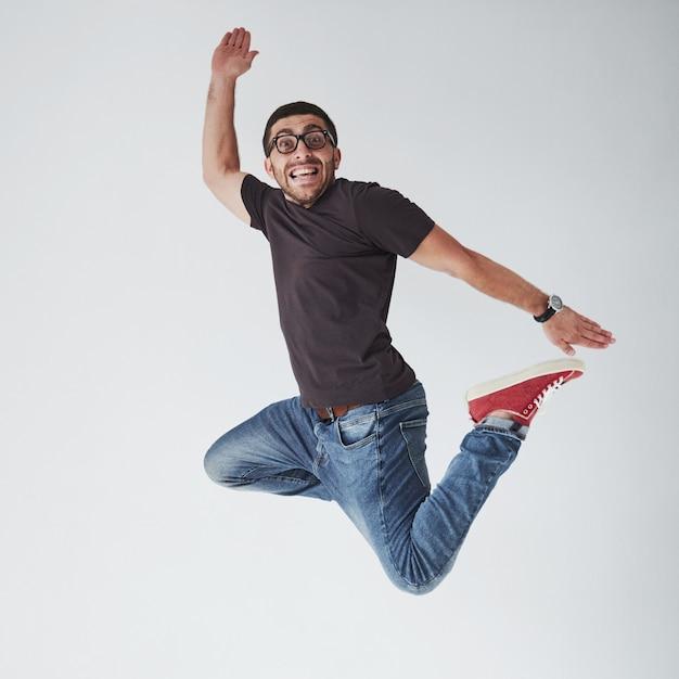 Toevallig gekleed beeld van het vrolijke jonge mens springend over wit Gratis Foto