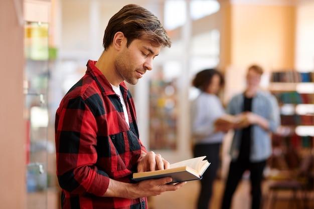 Toevallige student die met boek taken of tekst bekijkt vóór les of examen in universiteitsbibliotheek Premium Foto