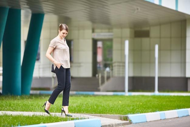 Toevallige vrij jonge vrouw die onderaan de stedelijke dag van de straatzomer loopt. zwarte jeans, schoenen met hoge hakken Premium Foto