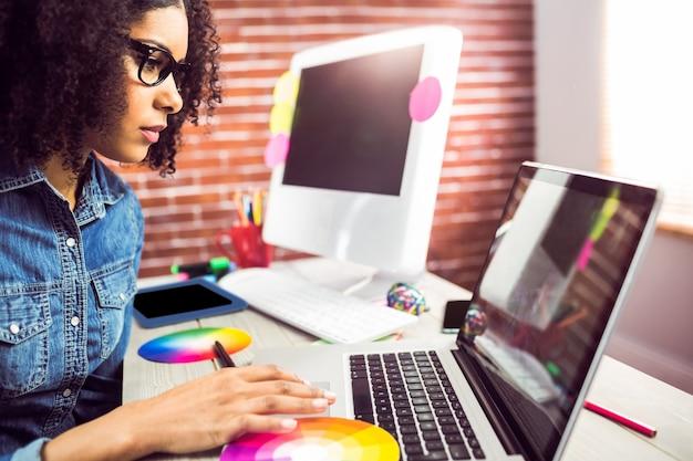 Toevallige vrouwelijke ontwerper die laptop met behulp van Premium Foto