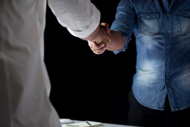 Toevallige zakenlieden die handdruk maken tijdens de vergadering bij nacht Premium Foto