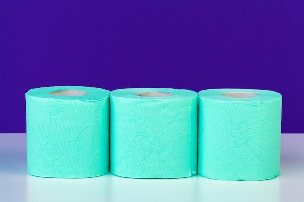 Toiletartikelen. rollen groen toiletpapier op paars Premium Foto