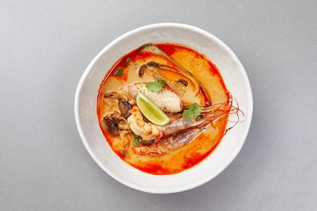 Tom yam, garnalen en vis in tomatensaus met kruiden en limoen, zeevruchtensoep Premium Foto