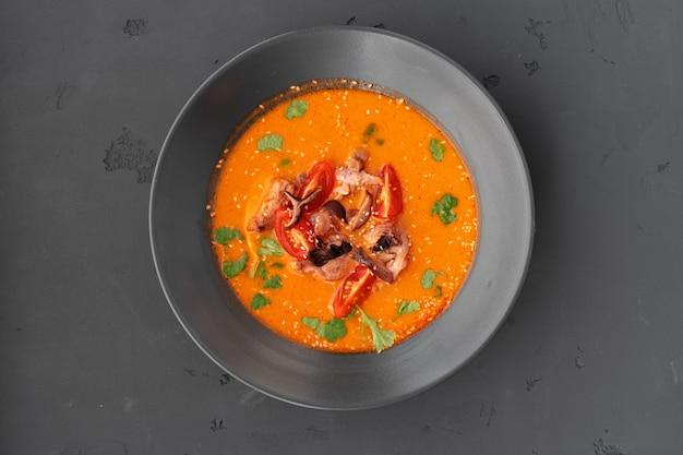 Tom yam thaise soep in zwarte kom die op grijs wordt gediend Premium Foto