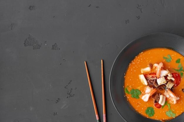 Tom yam thaise soep in zwarte kom geserveerd op een grijze achtergrond bovenaanzicht Premium Foto