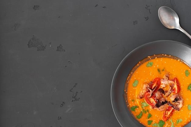 Tom yam thaise soep in zwarte kom geserveerd op een grijze achtergrond Premium Foto
