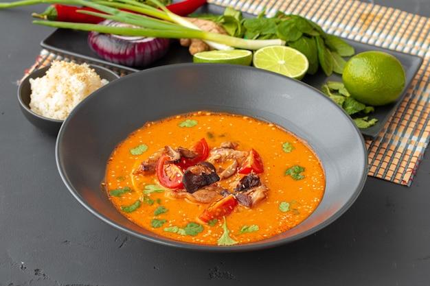 Tom yam thaise soep in zwarte kom op grijze tafel close-up Premium Foto