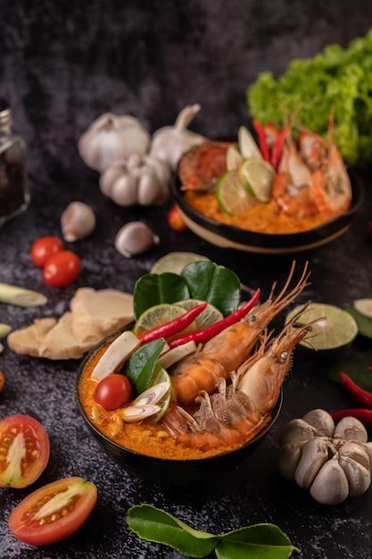Tom yum kung in een kom met tomaat, chili, citroengras, knoflook, citroen en kaffir limoenblaadjes Gratis Foto