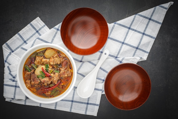 Tom yum, thais eten, hete, pittige en zure gestoofde rundvleessoep in kom met witte keramische lepel, lege houten kommen en tafelservet op donkergrijze tafel Premium Foto