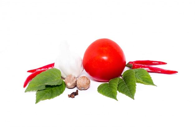 Tomaat met peper en knoflook op witte achtergrond, samenstelling van tomaten en kruiden hoogste mening Premium Foto