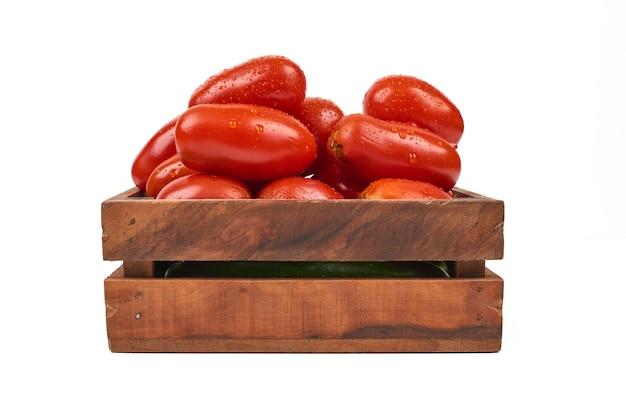 Tomaten in houten dienblad op het wit. Gratis Foto