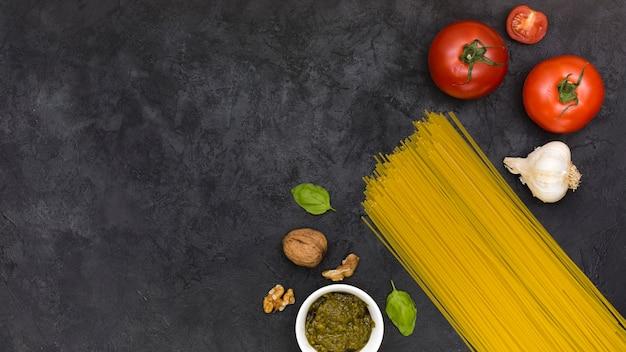 Tomaten; knoflook bol; basilicum; walnoten; saus en spaghetti op zwarte gestructureerde achtergrond Gratis Foto