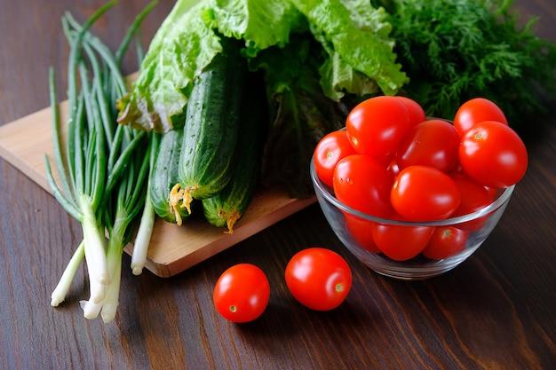 Tomaten, komkommers, groene salade en uien. zelfgemaakte biologische groenten. Premium Foto