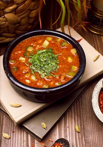 Tomatencourgette groentesoep met kruiden in zwarte kom op de boeken Gratis Foto