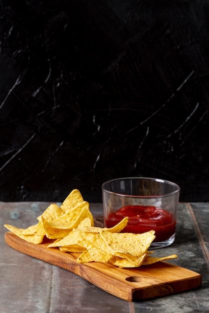 Tomatensaus op glazen kom en nachos op houten bord Gratis Foto